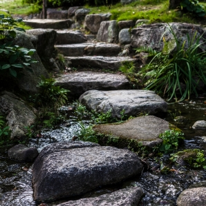 Closeup of a large stone pathway with greenery on each side